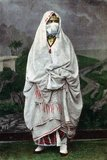Photograph of a veiled woman - presumably an Arab or Bedouin - of Algeria produced as a souvenir for the nascent European tourist market. market, c.1900.